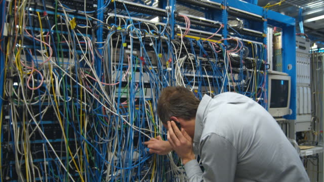 MS Man talking on mobile phone while trying to connect cable into wall of servers, Sydney, Australia
