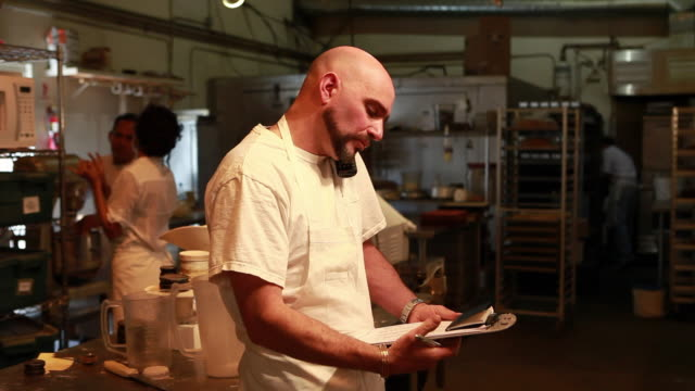 stockvideo's en b-roll-footage met ms man talking on phone and writing down order in kitchen / santa fe, new mexico, usa - draadloze telefoon