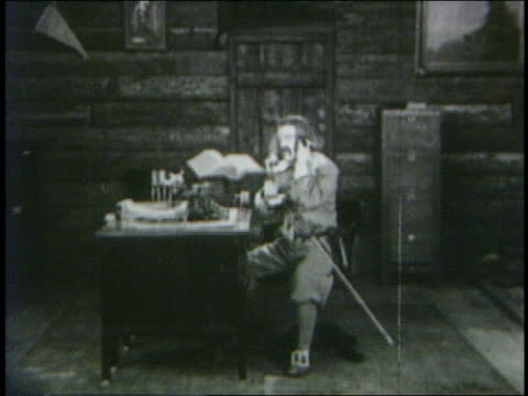 vídeos de stock, filmes e b-roll de b/w 1923 man (snub pollard) talking on telephone in cabin - 1923