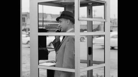 man talking on telephone in phone booth on street - telefonzelle stock-videos und b-roll-filmmaterial