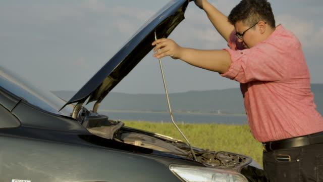 vidéos et rushes de homme parlant au téléphone à côté d'une voiture cassée. - trébucher