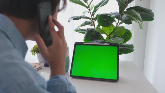vídeos de stock, filmes e b-roll de homem falando telefone enquanto olha para o tablet digital de tela verde em branco em pé na mesa de trabalho em casa para simular, modelo, conceito de tecnologia - digital tablet