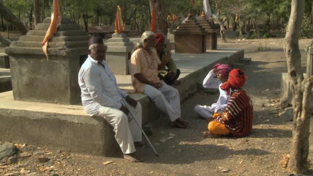 ws zi ms man talking sitting by shrine / rajkot, india - auf dem boden sitzen stock-videos und b-roll-filmmaterial