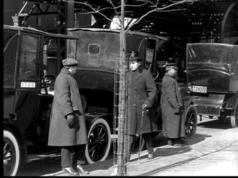 stockvideo's en b-roll-footage met b/w, ms, man talking to cab drivers waiting on street, 1924 - 1924