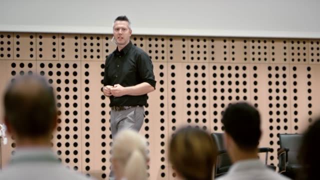 mann im gespräch mit dem publikum im konferenzsaal - konferenz stock-videos und b-roll-filmmaterial