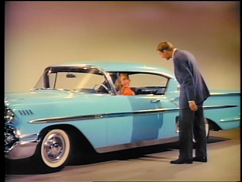 vídeos de stock e filmes b-roll de 1958 man talking to woman in chevrolet impala in showroom / commercial - general motors