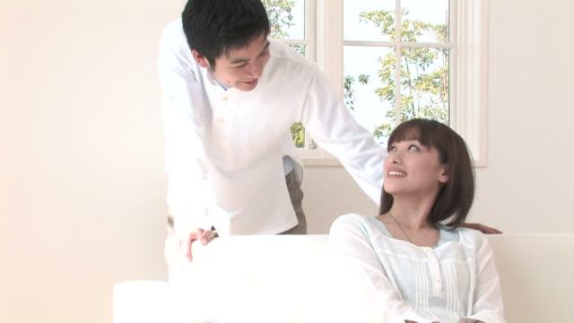 zo man talking to woman sitting on sofa - 向かい合わせ点の映像素材/bロール