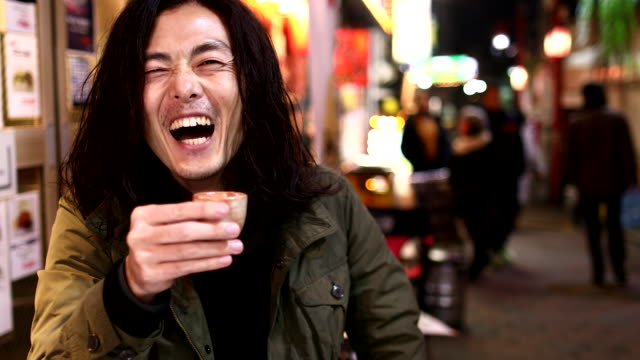 a man talking with a friend at the seat in front of the izakaya - one mid adult man only stock videos & royalty-free footage