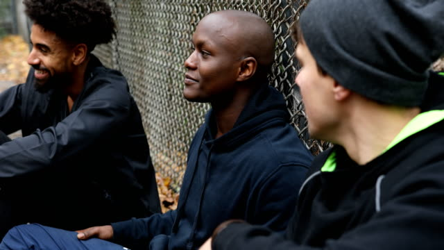 Man talking with his soccer team against fence