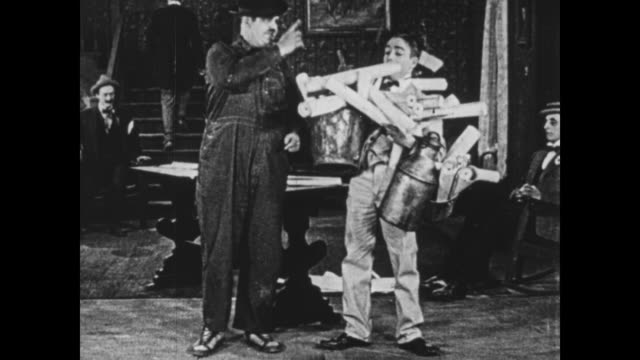 vidéos et rushes de 1925 man (oliver hardy) talks congenially with front desk man while accidentally hitting his helper in the face - 1925