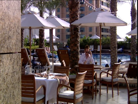 vídeos de stock e filmes b-roll de man talks on mobile phone by poolside of luxury hotel dubai - ao lado da piscina