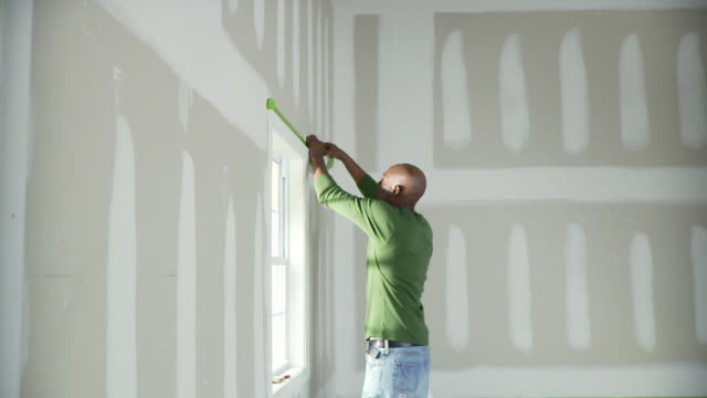 MS, Man taping window for painting, Plainfield, New Jersey, USA