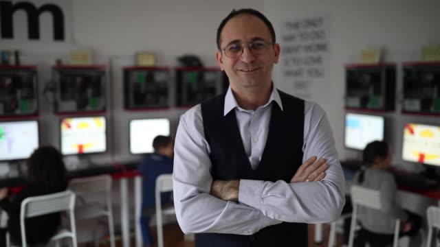 vídeos y material grabado en eventos de stock de profesor de hombre de pie en el aula moderna de la escuela de computación - brazos cruzados