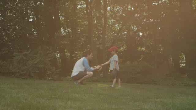 Man teaches boy baseball in backyard