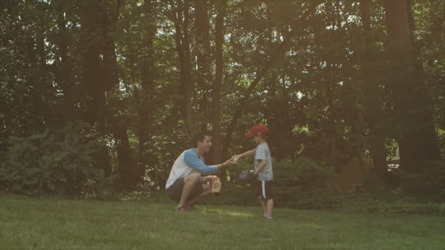 man teaches boy baseball in backyard - catching stock videos & royalty-free footage
