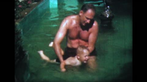 vidéos et rushes de 1957 man teaches son to swim in shallow pool - film d'amateur
