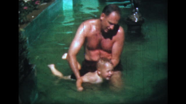1957 man teaches son to swim in shallow pool - lernen stock-videos und b-roll-filmmaterial