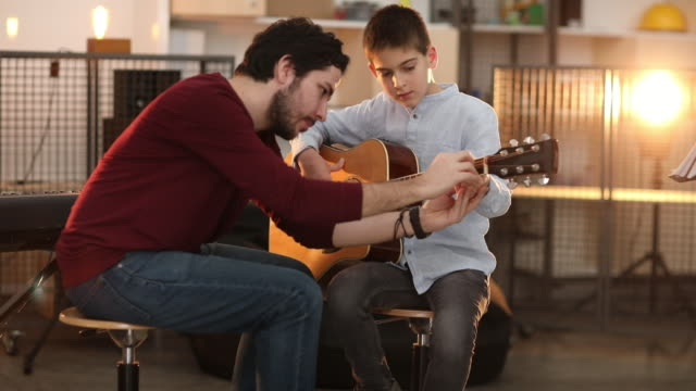 man teaching a little boy how to play guitar - classroom stock videos & royalty-free footage