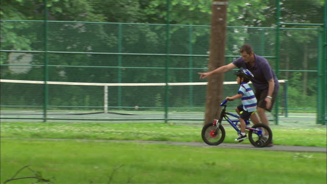 WS Man teaching boy how to ride bicycle in park/ Fanwood, New Jersey