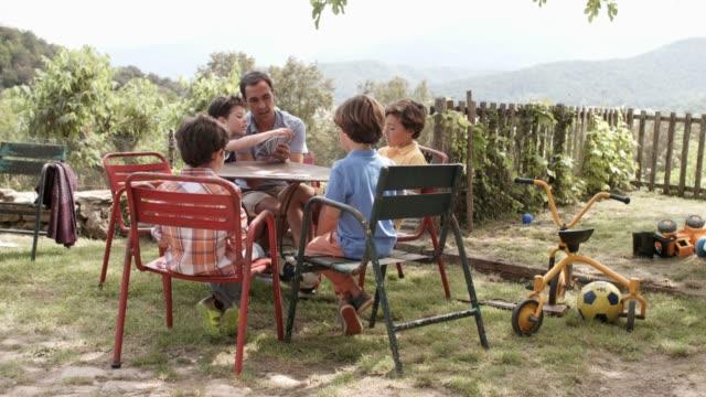 vídeos y material grabado en eventos de stock de hombre enseñando a los niños a jugar a las cartas en el patio - jardin