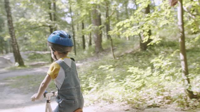 vídeos de stock, filmes e b-roll de homem ensinando seu filho a andar de bicicleta - teaching