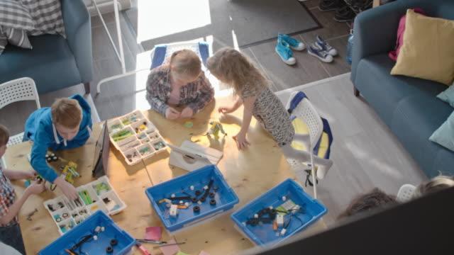 Man teaching kids how to build robots