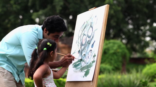 Man teaching painting to his daughter on a easel