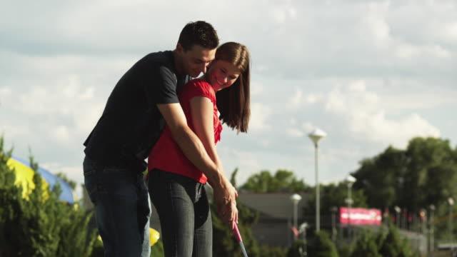 ms man teaching woman swinging golf club on golf course / orem, utah, usa  - orem utah stock videos & royalty-free footage