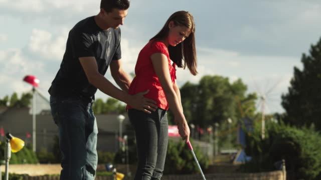 ms tu man teaching woman swinging golf club on golf course / orem, utah, usa - orem bildbanksvideor och videomaterial från bakom kulisserna