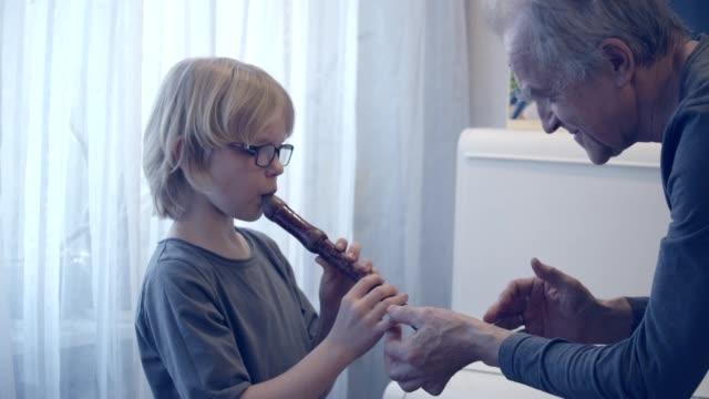 vidéos et rushes de homme (grand-père) enseignant le jeune garçon comment jouer de la flûte. - lunettes de vue