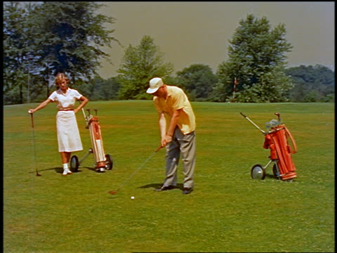 1955 man teeing off on golf course as bored woman stands with golf club in background - teeing off stock videos & royalty-free footage