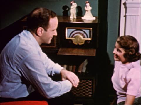 1950 man + teen girl sitting in living room talking + listening to radio / industrial - radio stock videos and b-roll footage
