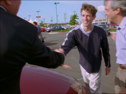 Man + teenage son in new car lot shaking hands with salesman + hugging