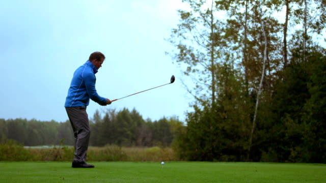 man tees off at a golf course - drive ball sports stock videos & royalty-free footage
