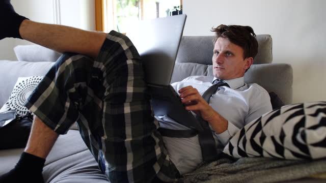 ds man telelavoro a casa, posa e lavoro sul divano - camicia video stock e b–roll