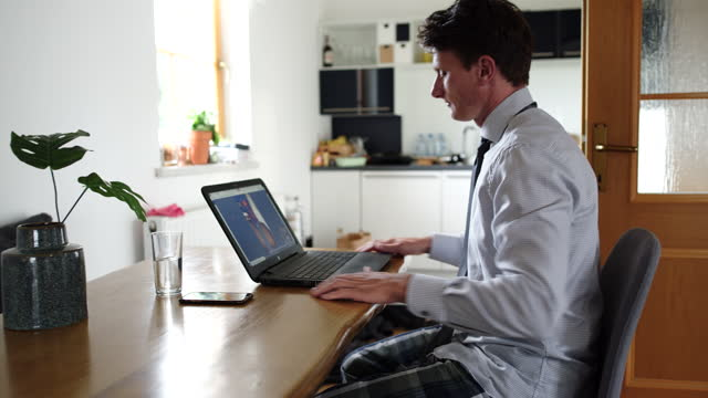 ws man telecommuting at home, working on a laptop in the kitchen - pyjamas stock videos & royalty-free footage