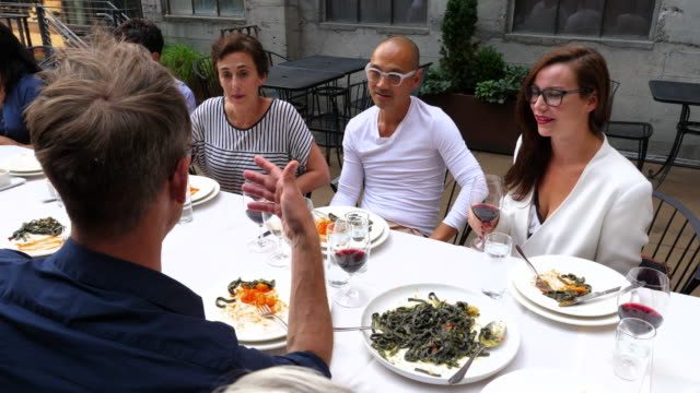 td pan man telling a story to friends during family style meal on restaurant patio - gente comune video stock e b–roll