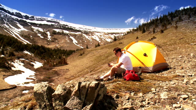 man tenting in mountains, talks on mobile - remote location stock videos and b-roll footage
