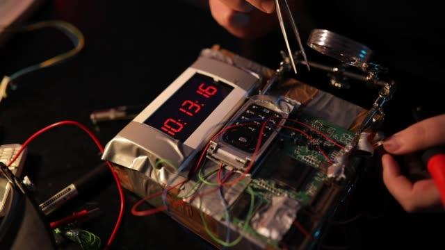 vídeos de stock, filmes e b-roll de terrorista do homem que constrói uma bomba de tempo - explosivo