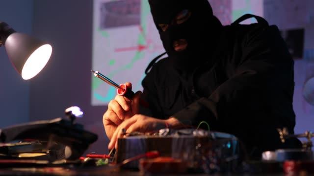 vídeos y material grabado en eventos de stock de hombre terrorista haciendo una bomba en el taller - haz de luz