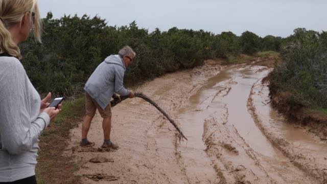 Man tests mud depth in road ahead