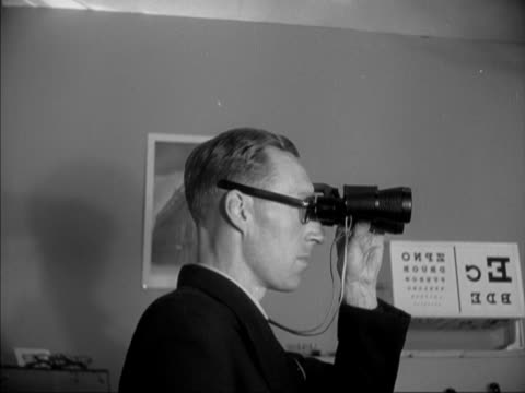 a man tests out a pair of binoculars at the opthalmic optical exhibition in london - binoculars stock videos & royalty-free footage