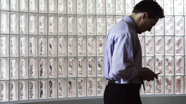 ms zo man text messaging in office hallway / orem, utah, usa - orem utah stock videos & royalty-free footage