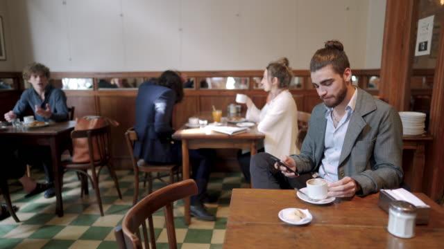 mann sms auf handy beim kaffeetrinken im café - 25 29 jahre stock-videos und b-roll-filmmaterial