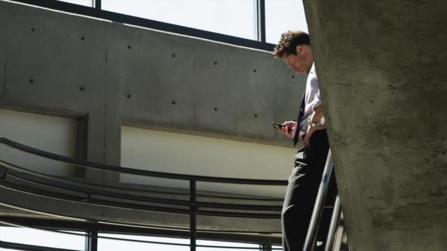 stockvideo's en b-roll-footage met ms ds man text messaging on office stairs / orem, utah, usa - orem utah