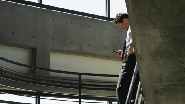 ms ds man text messaging on office stairs / orem, utah, usa - orem utah stock videos & royalty-free footage