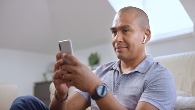 vídeos de stock e filmes b-roll de man texting and listening to music in his living room - latin american and hispanic ethnicity