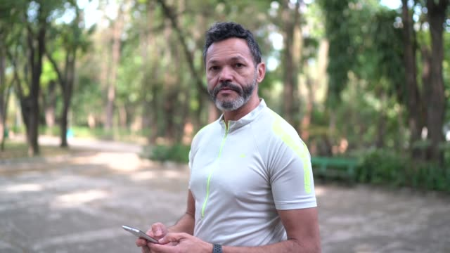 vídeos de stock e filmes b-roll de man texting using smartphone in a park - homens adultos