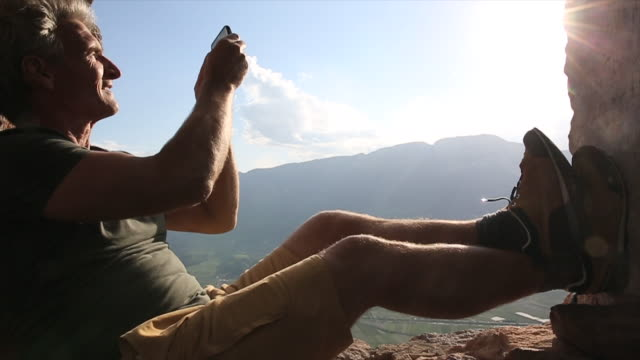 man texts/takes pic in ancient window frame, above mtns, sunrise - technophile stock videos & royalty-free footage