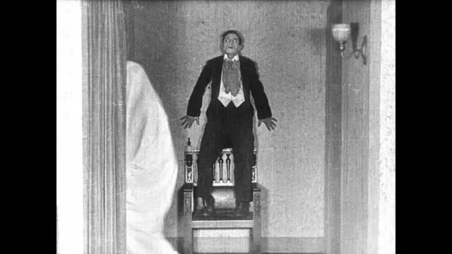 vídeos de stock, filmes e b-roll de 1922 man (buster keaton) thinks he sees a ghost in the mansion - electric lamp